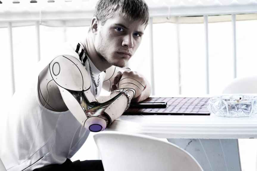 man with steel artificial arm sitting in front of white table
